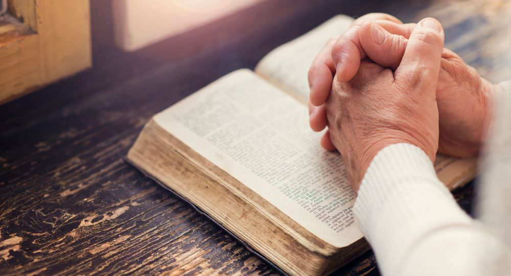 Praying with Bible - shutterstock