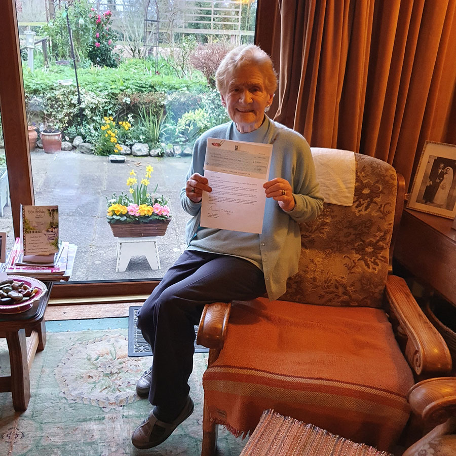 Iris Dungan holding up the letter from President Higgins to mark her 100th birthday this year